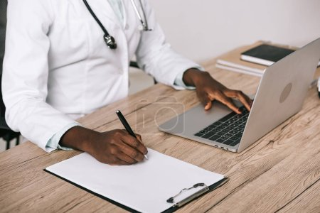 Photo for Cropped view of african american scientist writing on paper and typing on laptop - Royalty Free Image
