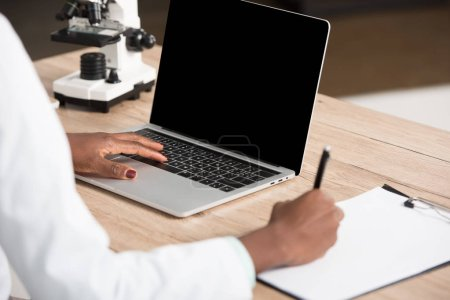 Photo for Cropped view of african american doctor writing on paper and using laptop with blank screen - Royalty Free Image