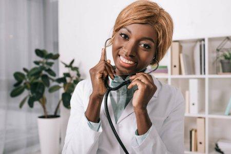 Photo pour Femme scientifique afro-américain avec stéthoscope dans les oreilles - image libre de droit