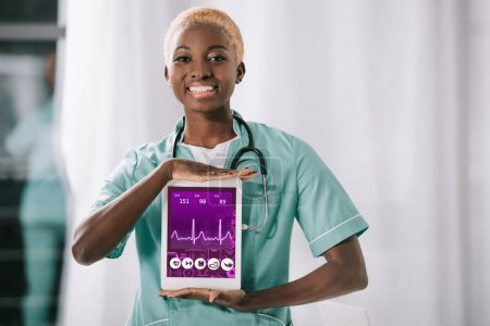cheerful african american nurse with stethoscope holding digital tablet with heartbeat rate on screen