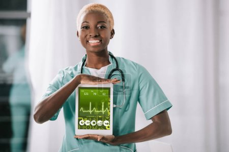 smiling african american nurse with stethoscope holding digital tablet with heartbeat rate on screen