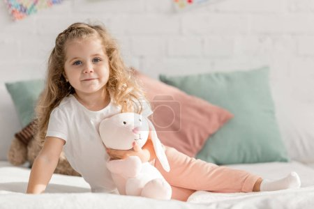Photo for Adorable kid sitting on bed with rabbit toy in children room and looking at camera - Royalty Free Image