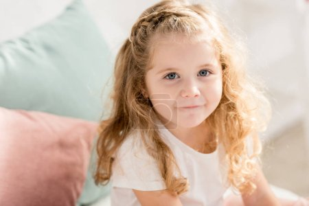high angle view of adorable kid with curly hair looking at camera in children room