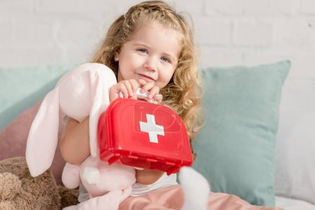 adorable kid holding first aid kit and rabbit toy in children room, looking at camera