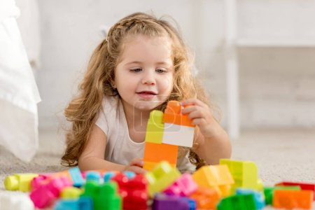 selective focus of adorable kid playing with colored plastic constructor on carpet in children room