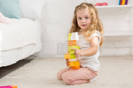 adorable kid playing with colored plastic constructor on carpet in children room and looking at camera