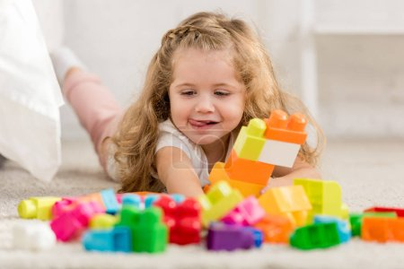 Photo for Happy adorable kid playing with colored plastic constructor on carpet in children room - Royalty Free Image