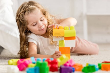 adorable child playing with colored plastic constructor on carpet in children room