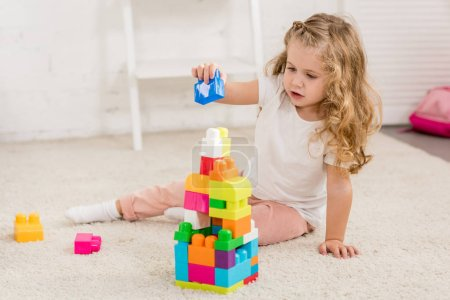 Photo for Adorable kid with curly hair playing with colored plastic constructor on carpet in children room - Royalty Free Image