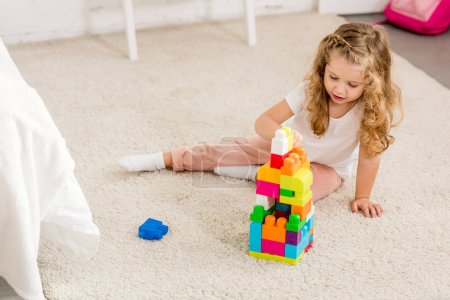 Photo for High angle view of adorable kid playing with colored plastic constructor on carpet in children room - Royalty Free Image