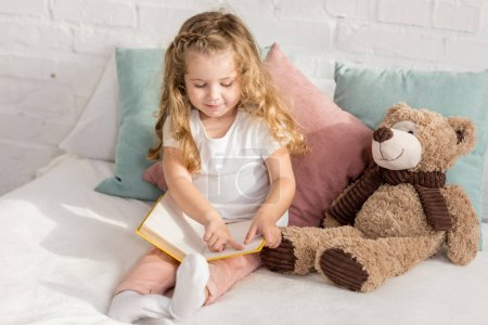 Photo for Adorable cheerful kid playing with teddy bear and reading book on bed in children room - Royalty Free Image