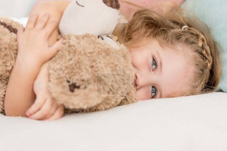 Photo for Cheerful adorable kid hugging teddy bear on bed in children room - Royalty Free Image
