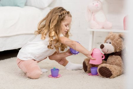 Photo for Adorable kid playing with teddy bear on floor in children room - Royalty Free Image