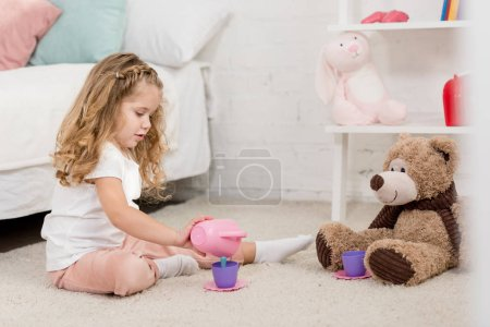 Photo for Adorable kid playing with teddy bear and plastic cups on floor in children room - Royalty Free Image