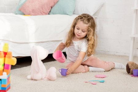 adorable kid playing with rabbit toy and plastic cups in children room