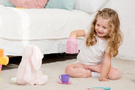 Photo for Adorable happy kid playing with rabbit toy and plastic cups in children room - Royalty Free Image
