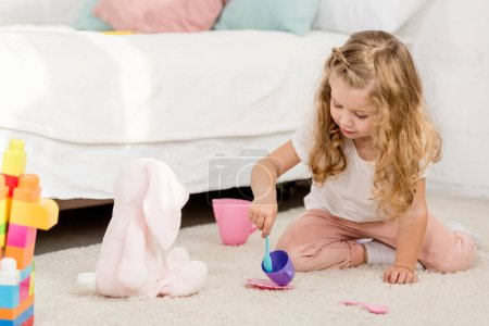 Photo for Adorable preschooler playing with rabbit toy and plastic cups in children room - Royalty Free Image