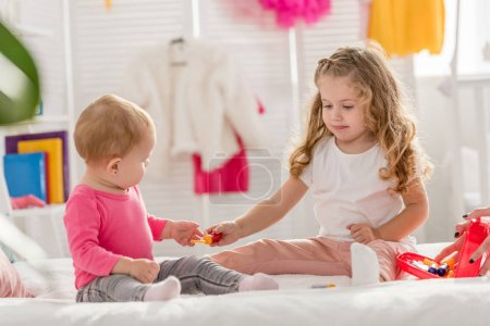 Photo for Adorable sisters playing with first aid kit on bed in children room - Royalty Free Image