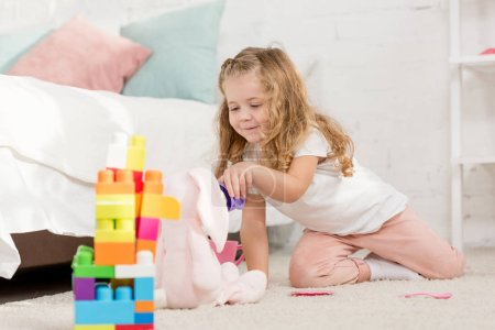 Photo for Adorable kid with curly hair playing with soft rabbit and plastic cups on carpet in children room - Royalty Free Image