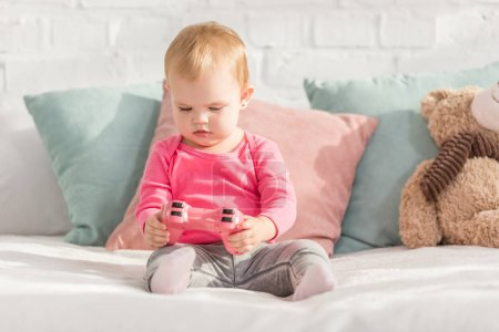 Photo for Adorable kid in pink shirt holding pink joystick on bed in children room - Royalty Free Image