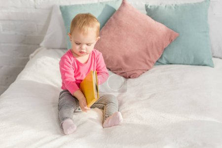 Photo for Adorable kid in pink shirt holding book on bed in children room - Royalty Free Image