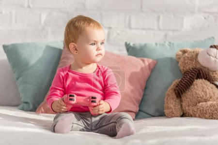Photo for Adorable kid in pink shirt holding pink joystick on bed in children room and looking away - Royalty Free Image