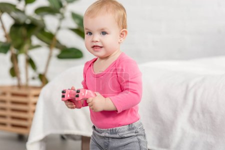 Photo for Cheerful adorable kid in pink shirt holding pink joystick near bed in children room - Royalty Free Image