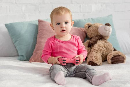 Photo for Adorable child in pink shirt holding pink joystick on bed in children room - Royalty Free Image