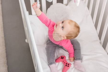 Photo for High angle view of adorable kid in pink shirt holding pink joystick in crib and reaching toy - Royalty Free Image
