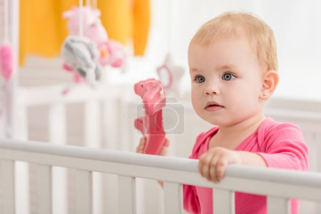 Photo for Adorable child in pink shirt holding pink joystick in crib - Royalty Free Image