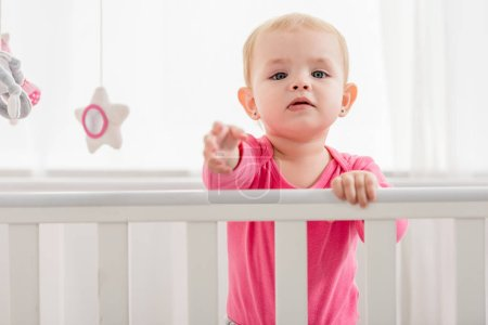 Photo for Adorable kid in pink shirt standing in crib and reaching hand to camera - Royalty Free Image