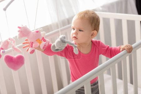 Photo for Adorable child in pink shirt standing in crib and touching toys - Royalty Free Image