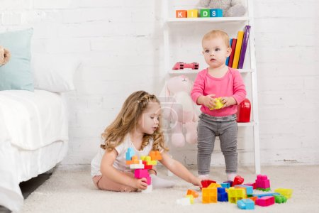 adorable sisters playing with constructor in children room