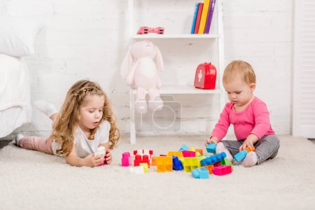 Photo for Adorable sisters playing with constructor on carpet in children room - Royalty Free Image