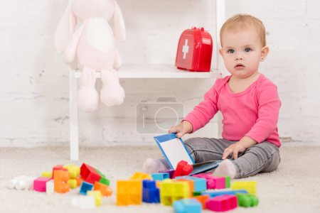 Photo for Adorable kid sitting on carpet and holding book in children room - Royalty Free Image