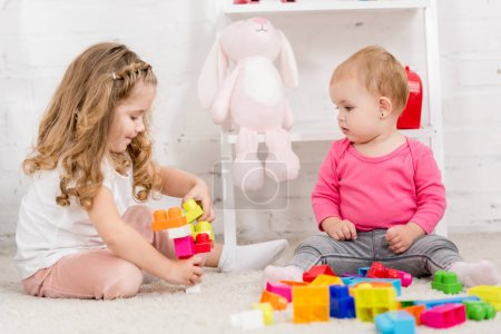Photo for Adorable sisters playing with constructor together on carpet in children room - Royalty Free Image