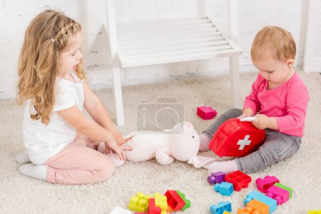 Photo for High angle view of adorable sisters playing with toys in children room - Royalty Free Image