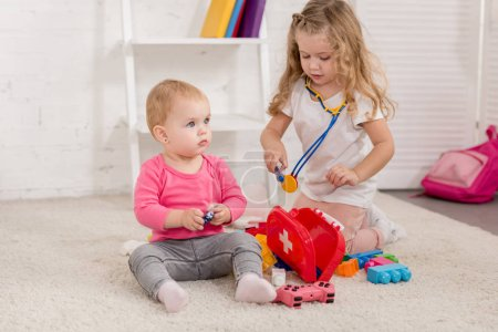 Photo for Adorable preschooler and toddler sisters playing with first aid kit in children room - Royalty Free Image