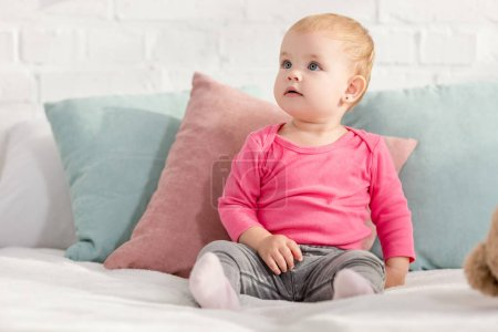 Photo for Adorable kid sitting on bed with pillows and looking up in children room - Royalty Free Image