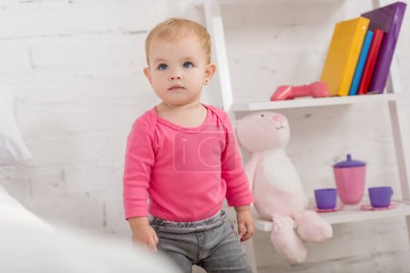 Photo for Adorable kid in pink shirt standing and looking up in children room - Royalty Free Image