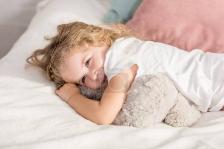 Photo for Smiling adorable happy kid lying on bed in children room and looking away - Royalty Free Image