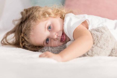 grimacing adorable happy kid lying on bed in children room and looking at camera