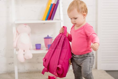 Photo for Adorable kid in pink shirt carrying pink bag in children room - Royalty Free Image