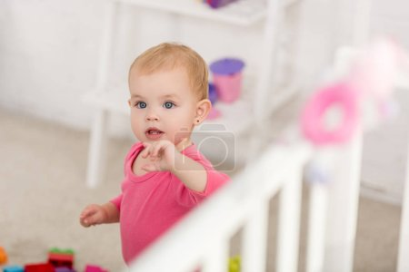 Photo for Selective focus of adorable kid in pink shirt standing near crib in children room - Royalty Free Image