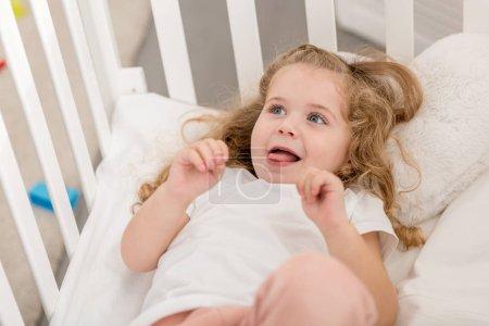 Photo pour Adorable gamin coller langue dehors et couché dans une crèche dans la chambre d'enfant - image libre de droit