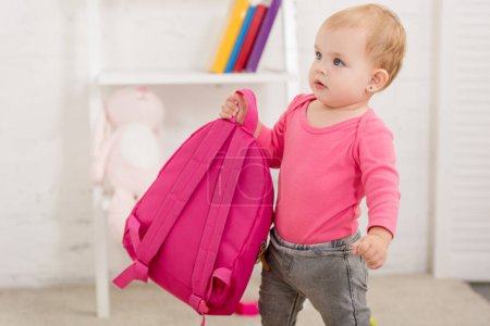 Photo for Adorable child in pink shirt carrying pink bag in children room - Royalty Free Image