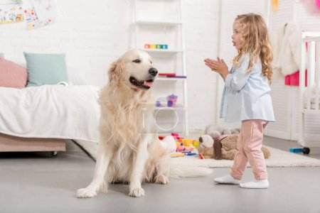 Photo for Adorable kid and golden retriever in children room - Royalty Free Image