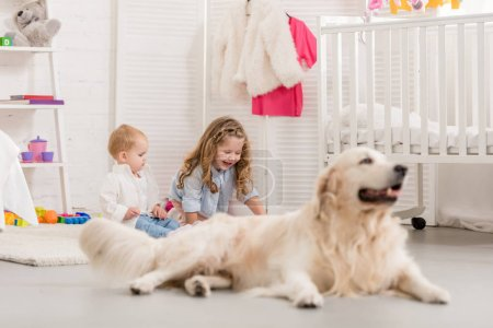 Photo for Selective focus of adorable sisters playing on floor, golden retriever lying near in children room - Royalty Free Image