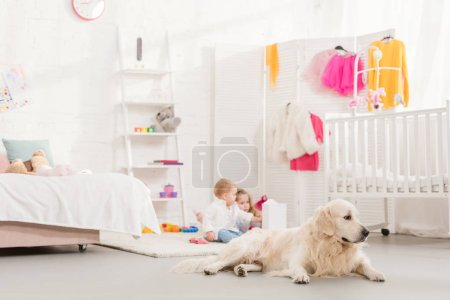 Photo for Adorable sisters playing with toys, golden retriever lying on foreground in children room - Royalty Free Image