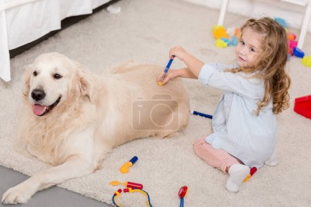 high angle view of adorable kid pretending veterinarian and examining golden retriever in children room